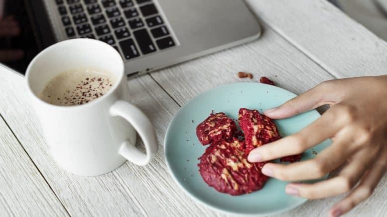 Teller Kekse und Kaffeetasse vor Laptop